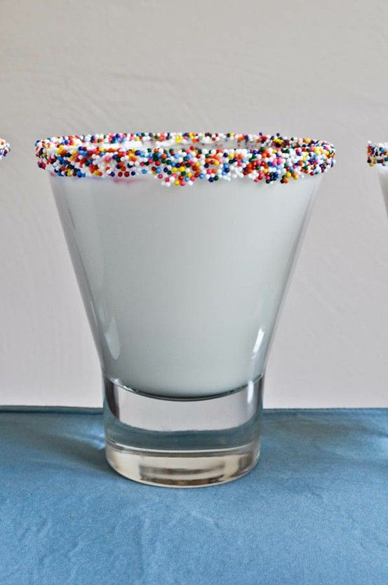 Wet the rim of a glass by  placing water in a bowl to the desired depth, dip in the glass them in another bowl of hundreds & thousands AKA sprinkles, dip and coat the rim. Fill with milk. Great kids birthday healthy drink idea