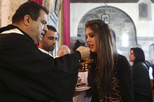 Mideast Iraq Christmas In this Wednesday, Dec. 24, 2014 photo, an Iraqi Christian woman takes communion during Christmas Eve mass in the Chaldean Church of the Virgin Mary in al-Qoush, northern Iraq, just 12 kilometers (7.5 miles) from the frontline, where Kurdish Peshmerga fighters battle the forces of the Islamic State group. Many of the worshippers are displaced from their homes after Islamic State militants swept through northern Iraq in August. (AP Photo)