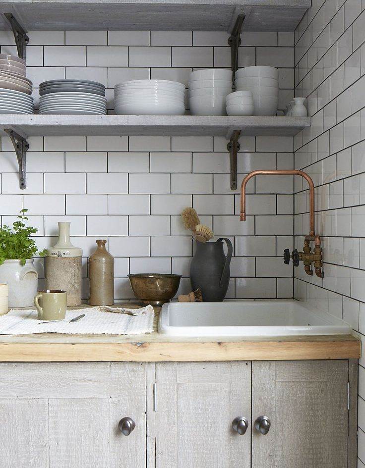 Thick slab of raw edge countertops, copper side-wall mounted wall faucet & inexpensive yet interesting glazed cabinets.