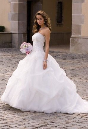 Captivate the crowd of on-seekers at your wedding day in this heavenly gorgeous strapless wedding dress made of plush organza and shaped in a classic ball gown silhouette. You'll feel and look the ultimate regal princess that you are in this stylish beauty, which features a beaded lace corset bodice, voluminous gathered skirt bottom and stunning, floor-sweeping cathedral train. Wear this fabulous dress with the right accessories such as a pair of peep-toe sandals, a pleated flap clutch…