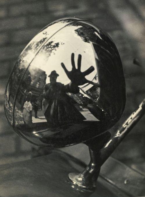 Kinszki Imre: Self-portrait in reflection of car headlight, 1930s