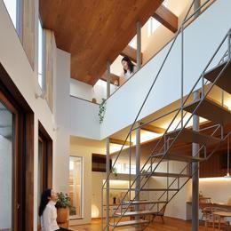 三角の吹抜けのあるチークの家  ( 奥沢の家 )の部屋 リビングのベンチに座り2階スタディコーナーを見上げる