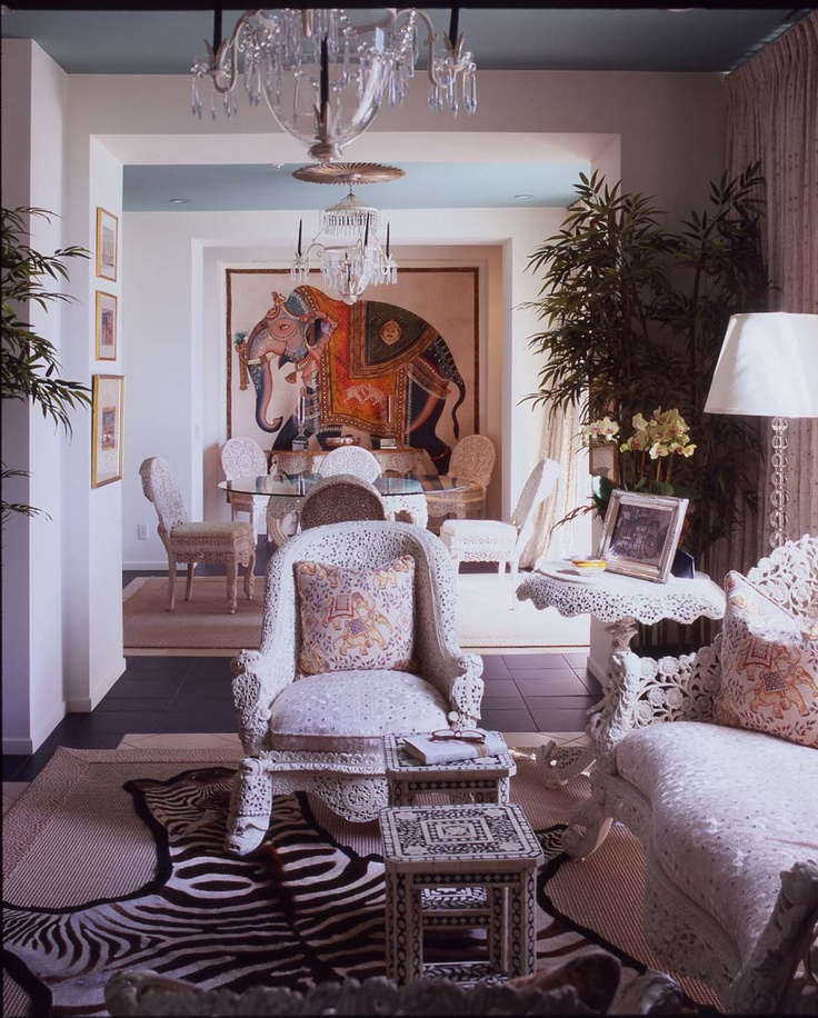 A VIEW DOWN AN ENFILADE OF ROOMS DESIGNED BY HUTTON WILKINSON, TONY DUQUETTE INC. TO RESEMBLE A HOUSE BOAT IN KASHMIR, USING ANTIQUE CARVED INDIAN FURNISHINGS, PAINTINGS, AND EMBROIDERED WHITE MIRROR CLOTH FABRIC.