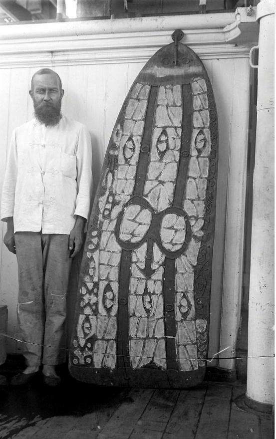 Dr. Lorentz poserend naast een Asmatschild. 1909-1910