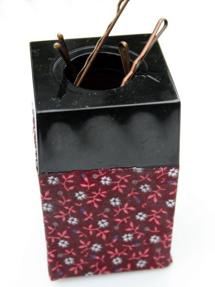 Raid your desk for an everyday office supply that will make it easy to have hairpins on hand for your next updo. A paper clip holder makes a clever magnetic container for storing bobby pins. Add fabric to the outside of the paper clip holder using Mod Podge. Then, simply wrap the fabric around the container like you would wrap a present (but skip the top). Fold the fabric on the bottom like the end of a present, and add Mod Podge under the fabric to keep it in place. Design by Kitty Vogt