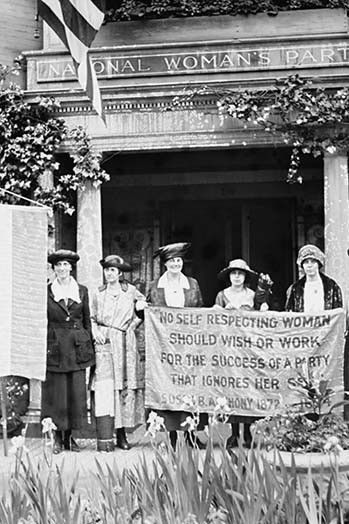 Suffragettes hold up banner in front of a building that has an architrave sign of the National Woman's Party; They claim to be ignored by the organization and hold up a protesting banner.