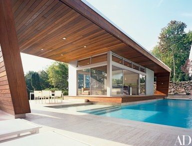 """""""The owners' first direction to us was to 'create something that's transparent, because we want to see through it,'"""" architect Gisue Hariri says of a contemporary, ipe-paneled poolhouse in Wilton, Connecticut, her firm designed for a couple and their two children, ages 12 and 14. """"The pool and structure become one."""" Outdoor furniture, Janus et Cie   archdigest.com"""