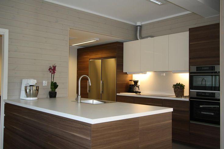 Kjøkkenet - en kjøkkenøy med vask foran i bildet og en lang kjøkkenbenk bak med både høyskap, underskap og overskap..