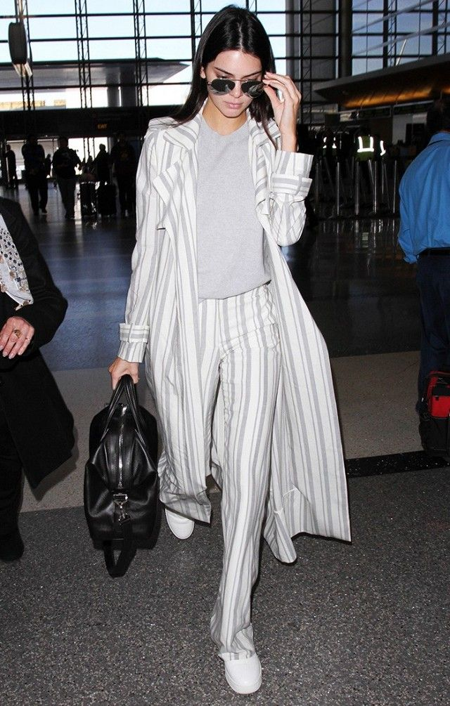 Kendall Jenner wears a gray top, striped coat, striped trousers, white sneakers, a black satchel, and aviator sunglasses