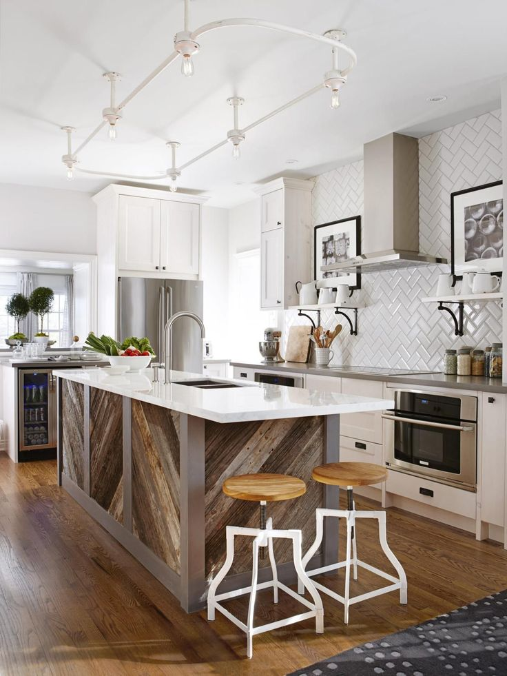 An island clad in reclaimed barn wood boards adds an interesting twist to this otherwise sleek kitchen. Designer Sarah Richardson chose the weathered boards for their texture and variations in color then had them installed in a herringbone pattern that coordinates with the same pattern in the tile backsplash.
