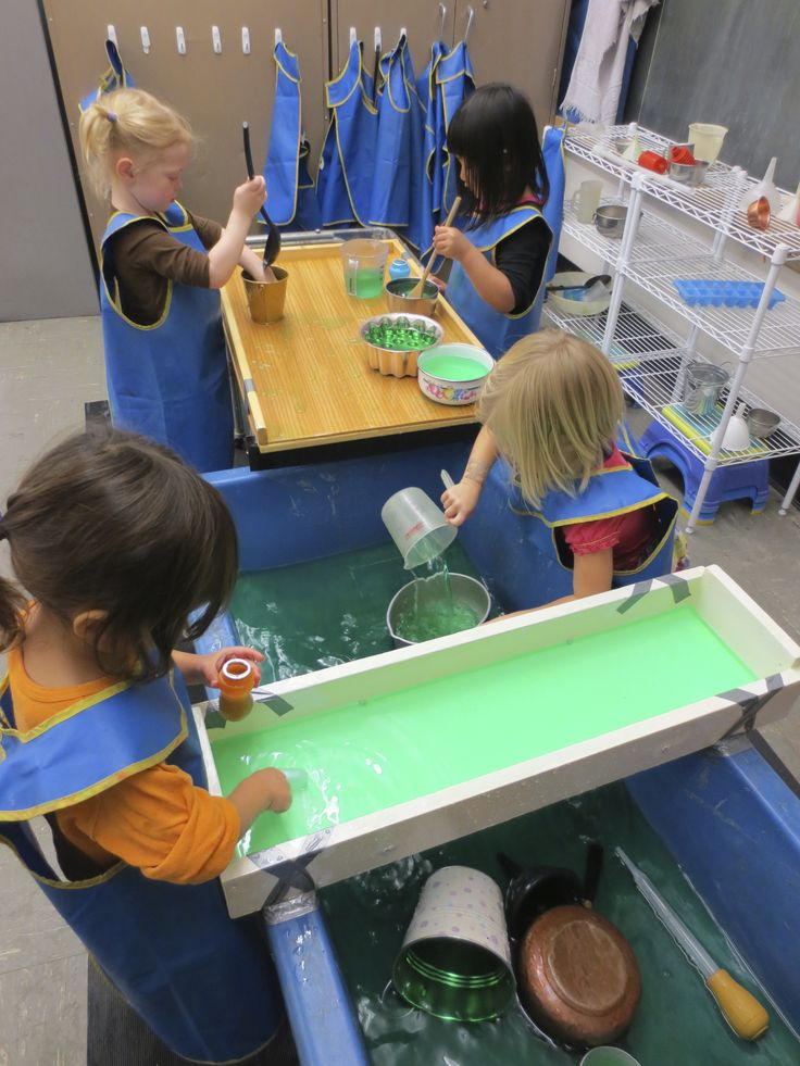 Large tray for mixing in the background.  It holds containers on a nice level on which the children can work.  If they spill it is slanted so water drops back into the water table.  You can also see the wooden tray spanning the blue table.  There are holes drilled in the sides so water leaks back into the water table and does not overflow.