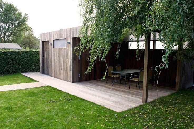Nova Concepts | Maatwerk modern tuinhuis met terrasoverkapping uitgevoerd in Padoek. Onder de overdekking is een padoek terras geplaatst.