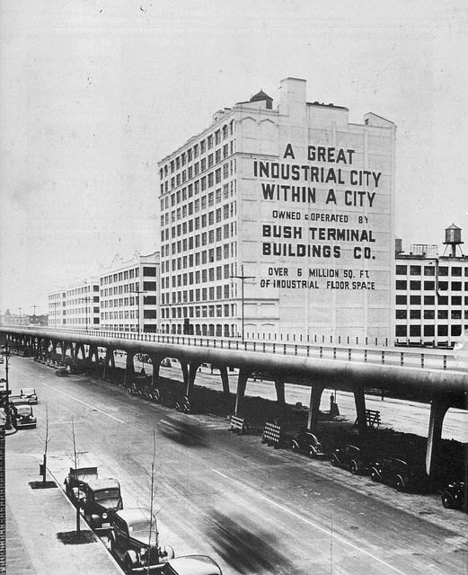 The original futuristic Gowanus Parkway completed but not open yet for traffic. Lots of 1930s cars parked. A warehouse proclaims 'A Great Industrial City Within A City'. Brooklyn, New York. 1940