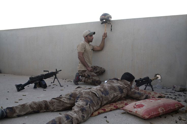An Iraqi special forces soldier puts up a helmet as a decoy as a sniper gets ready to fire on ISIS positions in Gogjali, on the eastern edges of Mosul, Iraq, on November 3, 2016.