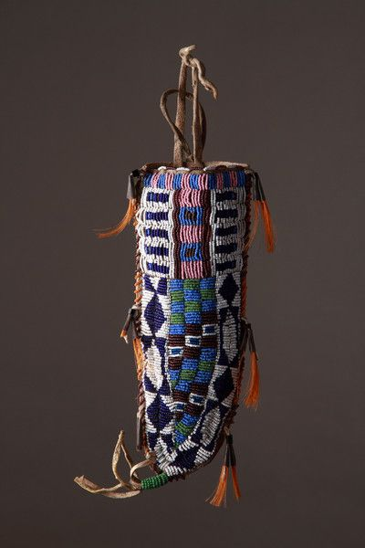 A Native American Indian Plains Dakota Sioux Beaded Knife Sheath the Reverse Painted in a Geometrical Pattern Buffalo hide, glass and steel trade beads, tin cones and horsehair Circa 1870 – 80