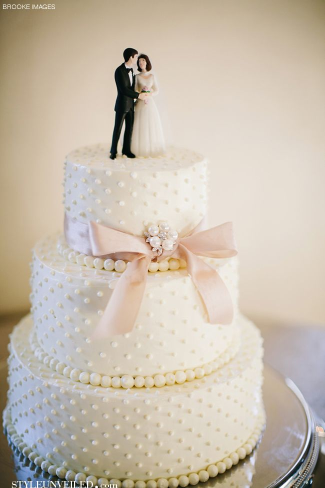 White Wedding Cake with Pearl Detailing and a Pink Bow