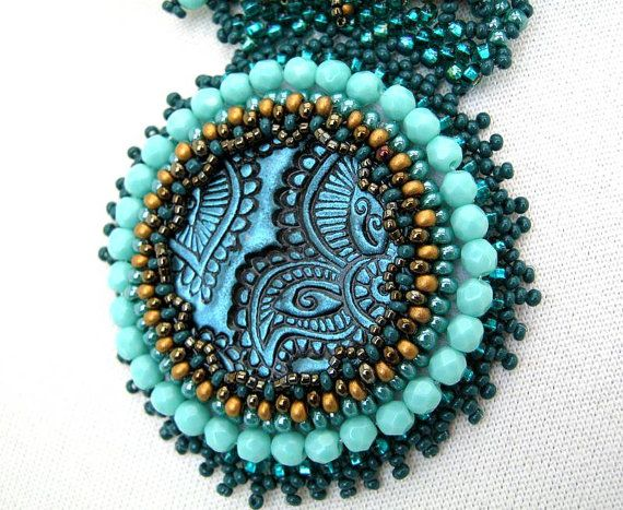 When I sit down to bead, I never know what Im going to make. I sort some beads together with different colors and sizes. When I find the most suitable color combination , from then its like a challenge, what can I create from them? As Im not using any patterns to make my jewelry, the result is an exciting riddle for me too.  I embroidered a beautiful handmade polymer clay cabochon for soft skin. The necklace is made of bright turquoise, teal and golden brown colors. Its an eye-catching wear…