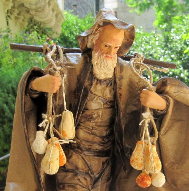 """Statue in Papier-mache: Farmer with """"Caciotta"""". This represents a piece of Salento's Tradition: livestocks and cheese factories. The production of cheese products has been for Centuries deeply rooted in Puglia, therefore a humble and old Shepherd who carries his cheeses."""