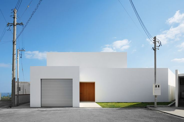 12 Minimalist Modern House Exteriors From Around The World | This simple white minimalist house features a grey garage door and a wood front door to give the house a modern look and warm up the all white exterior.