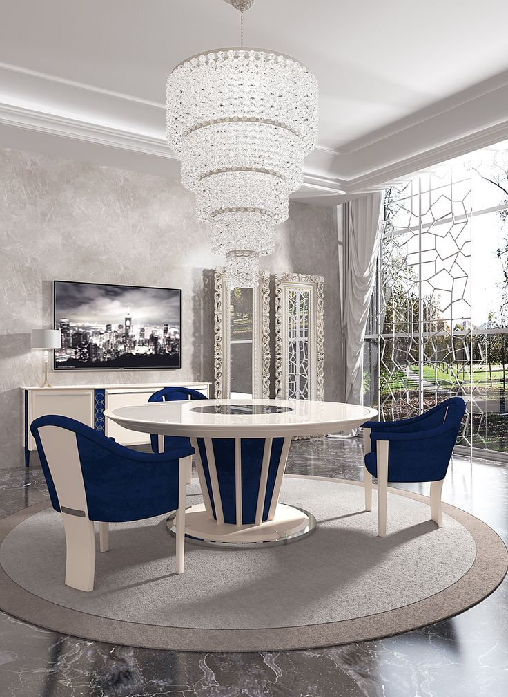 luxury dining room with round dining table complete of lazy susan in the middle, little blue armchairs, tv cabinet and baroque mirror frames