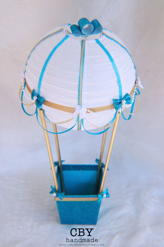 This handcrafted Hot Air Balloon centerpiece is made using an 8 white paper lantern that has been adorned with gold, white and blue ribbons. It is decorated with Pearl beads and blue satin ribbon draping and embellished with little mini bows. The lantern is attached to a blue glittered pail using wooden dowels that have been painted gold. The pail has been trimmed with gold ribbons and pearls to match.  **DIMENSIONS:**  Centerpiece: 16 tall x 8 wide Balloon: 8 Lantern  Pail: Top 4 x 4 / ...