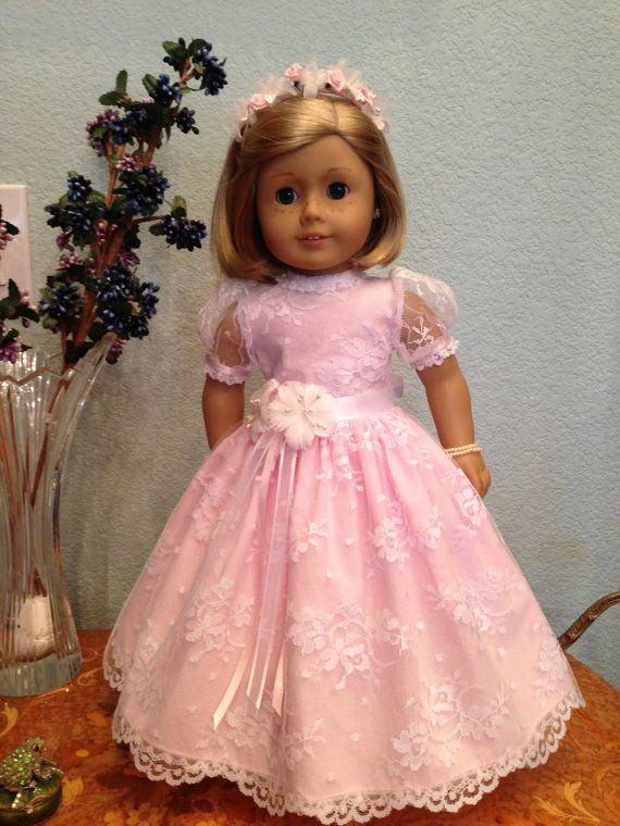 white lace over pink fabric communion or party dress with short sleeves and nice trim on the collar .