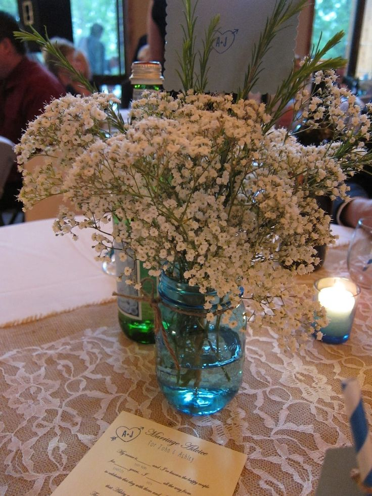 mason jar centerpiece with Baby's breath on a burlap and lace table runner