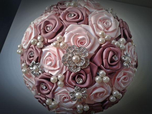 """Buquê de rosas em cetim e broches prateados e pérolas.  Os buquês são personalizados e montados de acordo com o gosto da noiva.  Eles são únicos sendo que nunca existirá um buque idêntico ao outro.  Composto de broches em tons de prata cravejados em strass, flores de cetim e pérolas.  Medidas:  65cm circunferência e 28cm diâmetro   A escolha do buquê de noiva é tão importante quanto a escolha do vestido.  O """"Bouquet de Broches"""" é uma verdadeira semi jóia"""