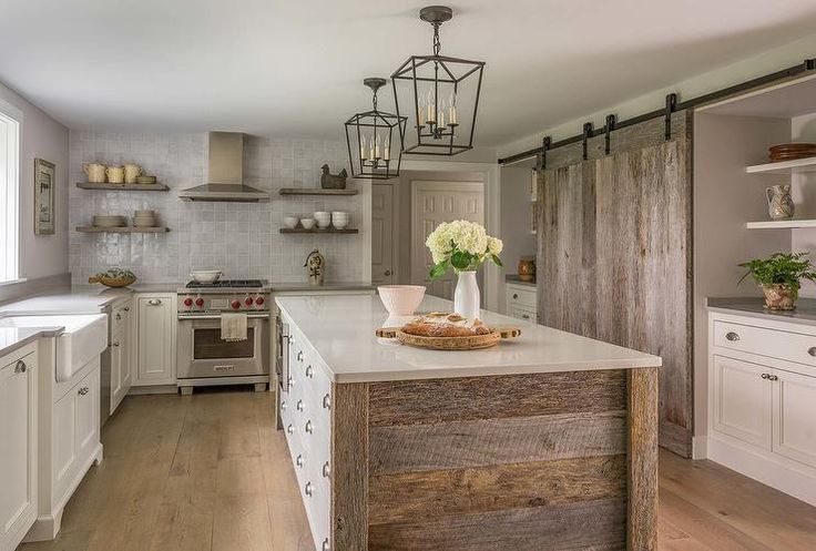 Two Darlana Mini Lanterns hang over a rustic wood island fitted with white apothecary style drawers accented with satin nickel cup pulls and a light gray quartz countertop.