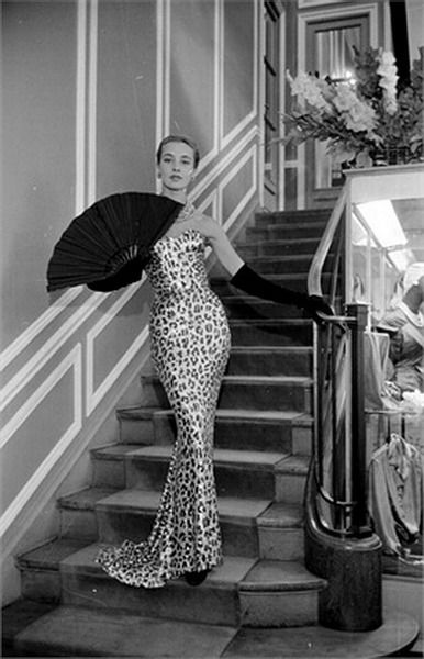 An alluringly curve-hugging gown from Christian Dior, 1953. fashion style couture designer long gown evening dress leopard spots cheetah sating column dress 50s photo print ad model