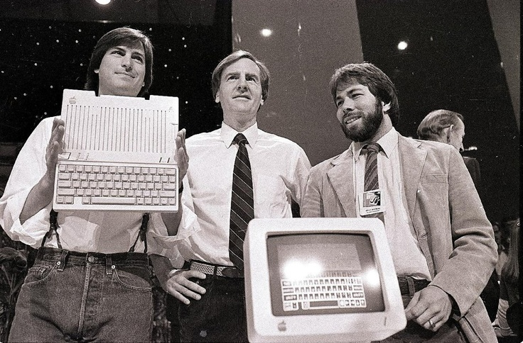 1984 - From left, Steve Jobs, chairman of Apple Computers, John Sculley, president and CEO, and Steve Wozniak, co-founder of Apple, unveil the new Apple IIc computer in San Francisco.. (AP Photo/Sal Veder, File)