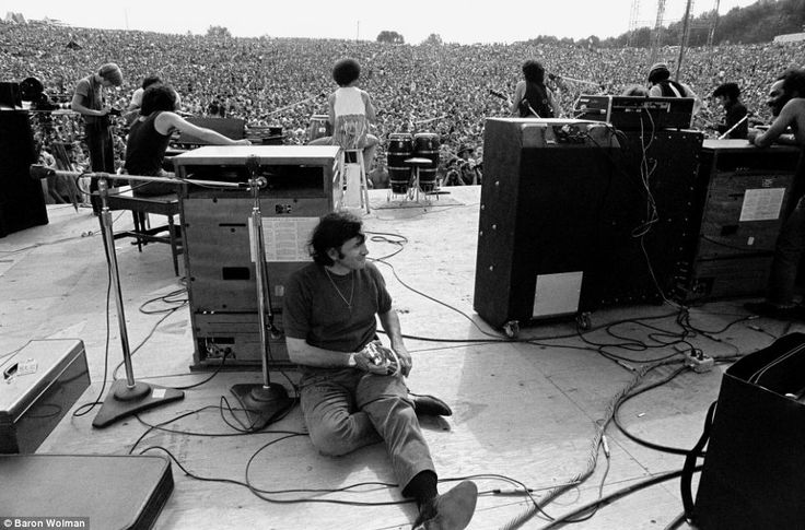 American impresario and rock concert promoter Bill Graham pictured onstage behind some speakers at Woodstock
