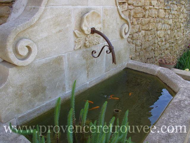 Ces poissons rouges ont élu domicile dans le bassin de cette fontaine en pierre naturelle.