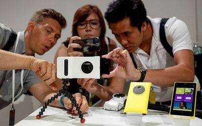 SNAPPING TO ATTENTION: Guests at the unveiling in New York of Nokia's new Lumia 1020 smartphone, which sports a  41-megapixel camera at the back. http://ow.ly/nh28r