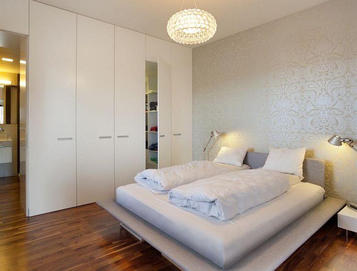 Ložnice majitele bytu je přístupná z obývacího pokoje. Skříňová stěna skrývá také dveře do šatny a do koupelny.