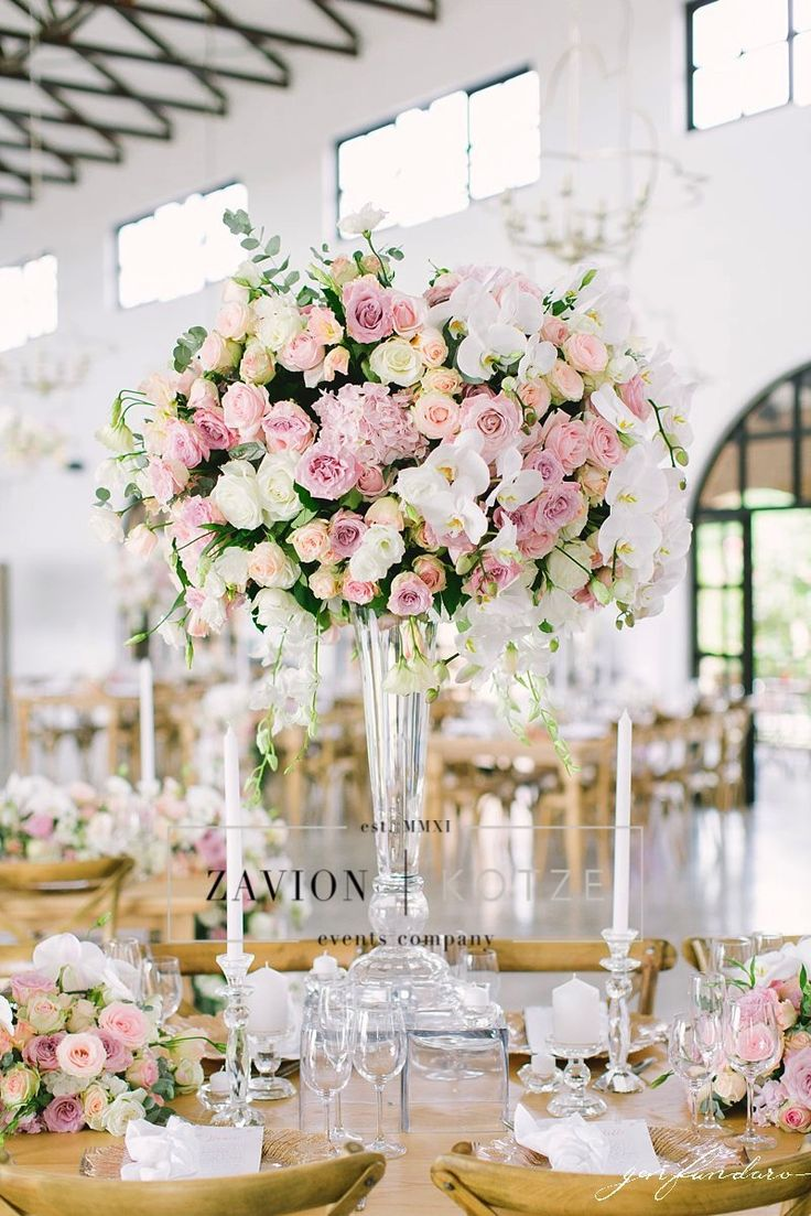 This stunning mass arrangement is everything! We love the roses, white, pink, raw wooden tables, white napkins, gold. wedding day, wedding table, best wedding ever, bridal table. royal wedding