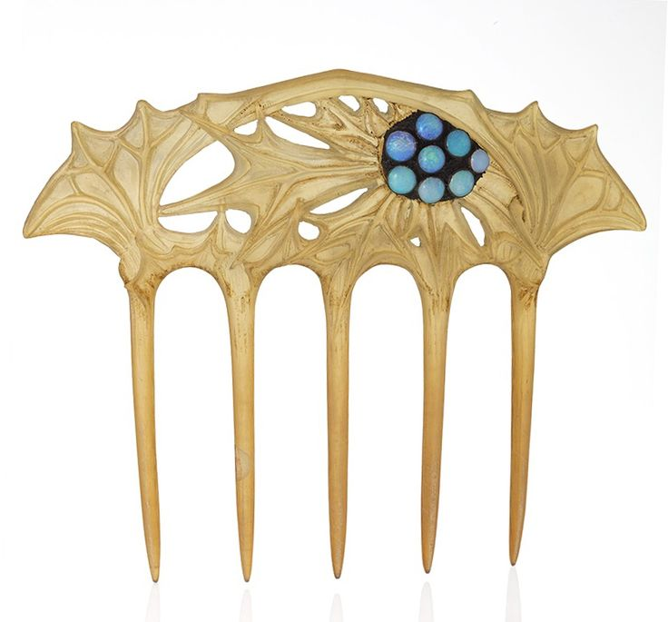 Lucien Galliard: A French Art Nouveau horn and metal hair comb with opals by Lucien Gaillard. The blond hair comb has 8 cabochon opals decorating the thistle motif carving. The Macklowe Gallery.