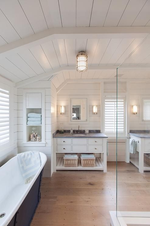Fantastic bathroom features a shiplap ceiling and walls lined with a freestanding tub placed under windows covered in plantation shutters atop sawn white oak wood floors.