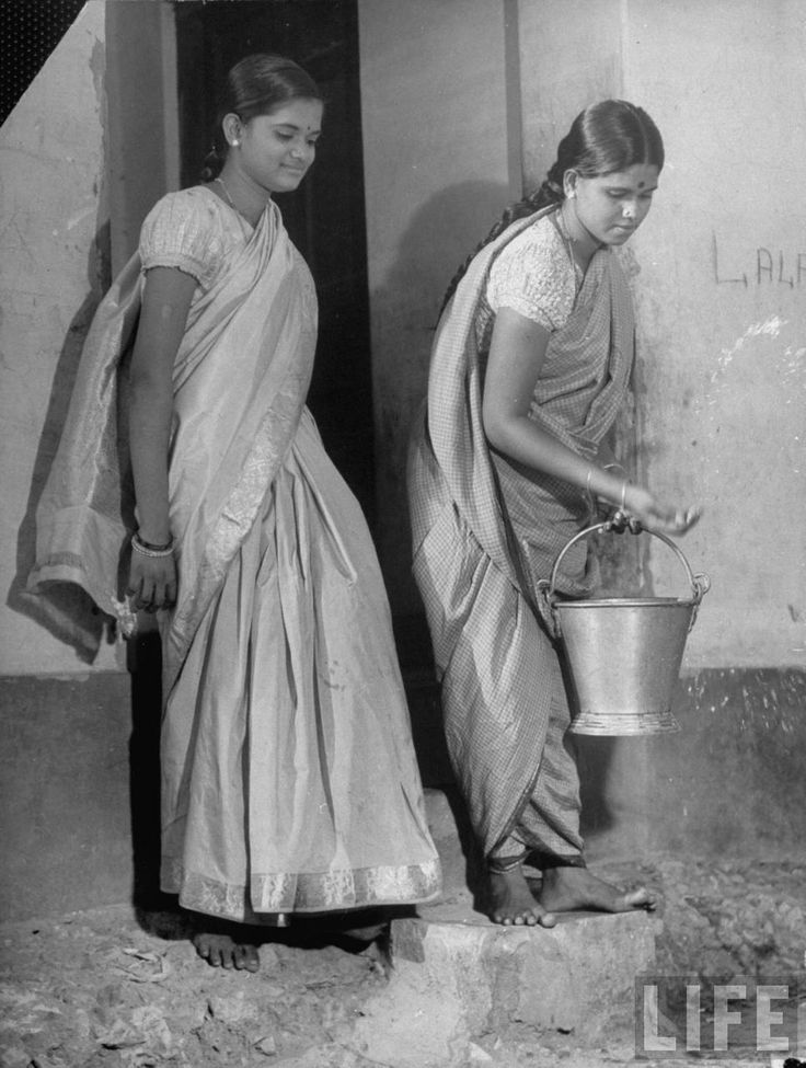 Two young Hindu women clad in their native dress, one carrying a bucket of water - 1946