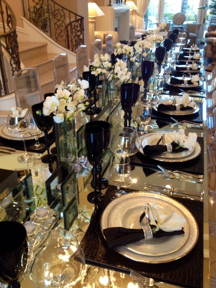 Elegant black alligator placemats with mother of pearl dinner ware. Tall solid black wine and champagne glasses along with mirrored vases holding calla lilies , dendrobium orchids. Chairs are acrylic with a 16' acrylic mirror dining table. Designed and collaborated by Andrew Joseph Designs and Paul Fenner Floral Designs