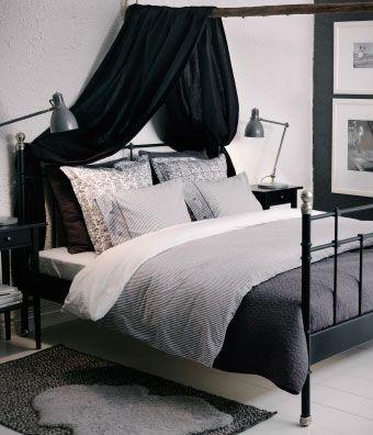 Cama SVELVIK em preto com mesas de cabeceira HEMNES e colcha ALINA em cinzento escuro com capas de almofada