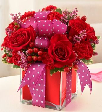 All Wrapped Up™ - Red- red roses, heather, red hypericum, red carnations and variegated pittosporum in a clear glass cube vase wrapped with a red foam strip $49.99
