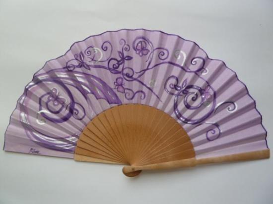 Abanico en tonos violeta con unas pinceladas en plata. Es de madera de abedul pulida y país de algodón , pintado a mano con un dibujo de espirales y mariposas.Medidas 23 x 43 cm