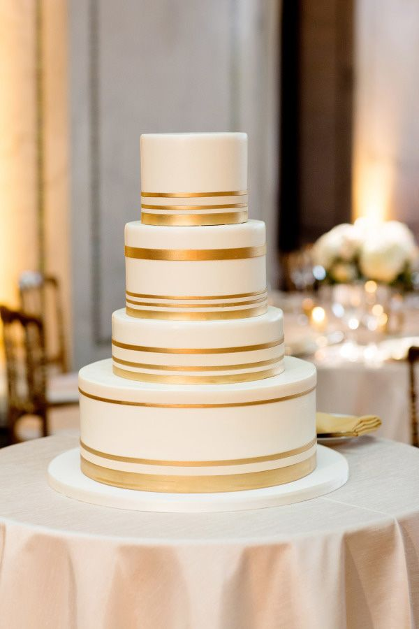 simple white wedding cake with shiny gold stripes