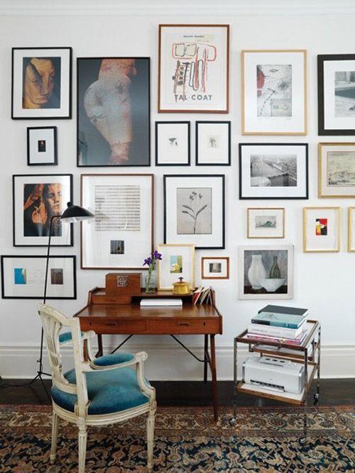 An art wall behind a wooden writing desk.