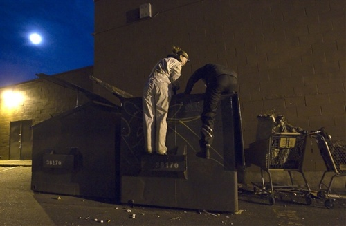 "Anna-Rae Douglass (left) and Robin Pickell who are both 'freegans'climb into a dumpster behind an organic grocery store in Coquitlam, British Columbia. A ""Freegan"" is someone who gathers edible food from the dumpster bins of grocery stores or food stands that would otherwise have been thrown away. (Ben Nelms / Reuters)"