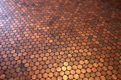 Mosaic copper flooring made of pennies. This has to be one of the least expensive per-square-foot floors ever. This might make an interesting backsplash as well.