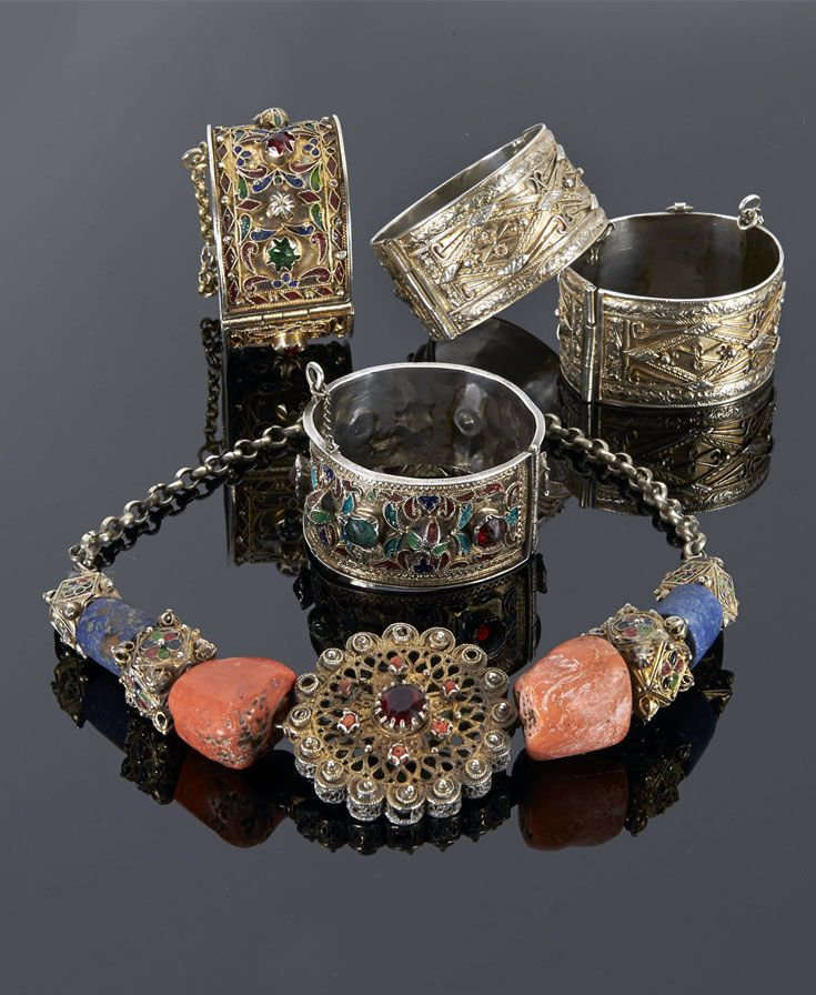Tunisia | Necklace; coral, lapis lazuli, garnet, gilt silver, enamel, coral and glass center piece on silver chain. A pair of matching silver gilt hinged bracelets and two gilt silver, enamel and glass cabochon bracelets. | 992€ ~ Sold (May '15)