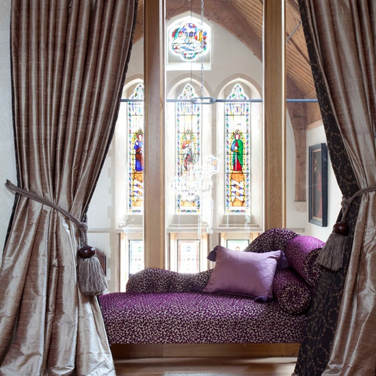 Step inside a glamorous converted church... A purple chaise lounge in the bedroom gallery enjoys a dramatic view of the double-height space with original and new stained-glass windows. Luxurious curtains provide privacy when needed. This chaise is upholstered in Evelyn fabric from Villa Nova. Photograph by Robert Sanderson... purple sofa, glass window,silver curtains.