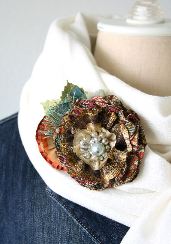 A fabric flower brooch in warm, autumn colors ... pretty mix of textiles and textures. Beautiful vintage beaded jewel center.